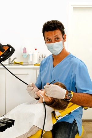 Young dentist in his office with female patent in chair  photo