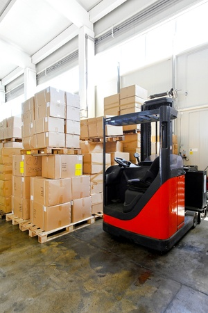 Red forklift in big warehouse with boxes  photo
