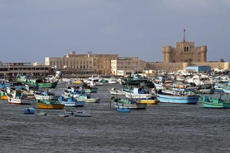 alexandria: ALEXANDRIA, EGYPT - FEBRUARY 28: Alexandria fortress on FEBRUARY 28, 2010. Fisherman boats and Citadel at sunny day in Alexandria, Egypt.  Editorial