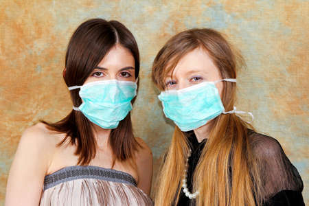 Two fashion girls with protective medical masks photo