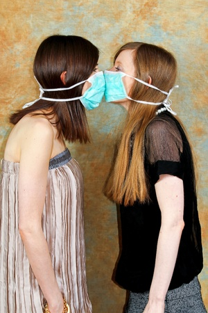 Two girls with protective masks against each other  photo