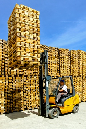 Man operating forklift lifting bunch of euro pallets  Stock Photo - 8906063