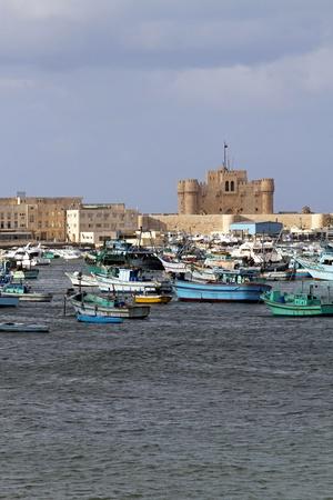 alexandria egypt: ALEXANDRIA, EGYPT - FEBRUARY 28: Alexandria fortress on FEBRUARY 28, 2010. Fisherman boats and Citadel at sunny day in Alexandria, Egypt.  Editorial