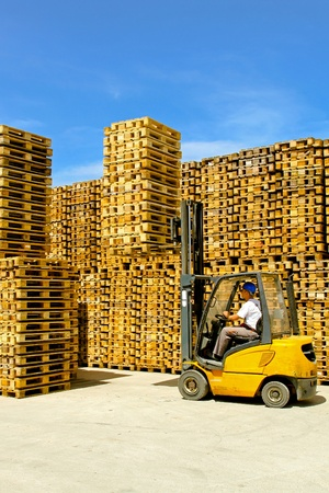 Forklift operator lifting bunch of euro pallets  Stock Photo - 9095277