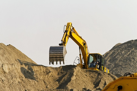 Excavator at big pile of sand at construction site Stock Photo - 9184983