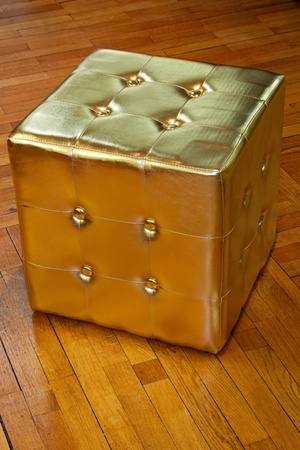 footstool: Small golden cube footstool at parquet floor  Stock Photo