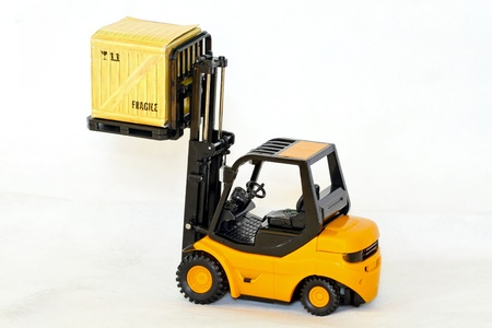Small forklift vehicle with loaded fragile crate