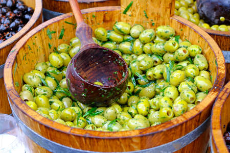 Green olives in wooden bucket sold on market Stock Photo - 9595626