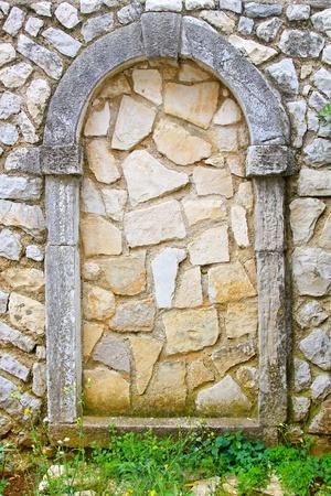 Permanent: Ommuurde boog deur permanent gesloten met stenen   Stockfoto