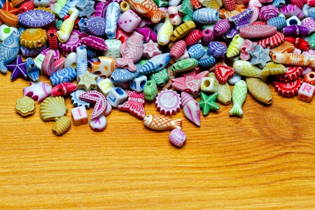 Multi colour beads assortment at wood background photo