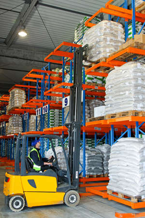 warehouse forklift: Descarga de mercanc�as con montacargas de almac�n de distribuci�n
