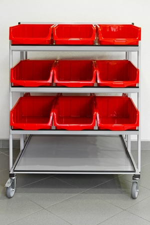 Supply trolley with plastic red boxes for storehouse  photo