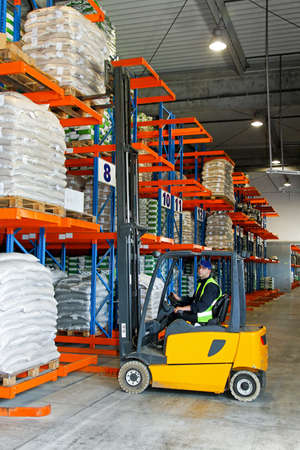 forklift driver: Loading goods with forklift in distribution warehouse