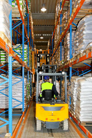 Yellow forklift between rows in distribution warehouse photo