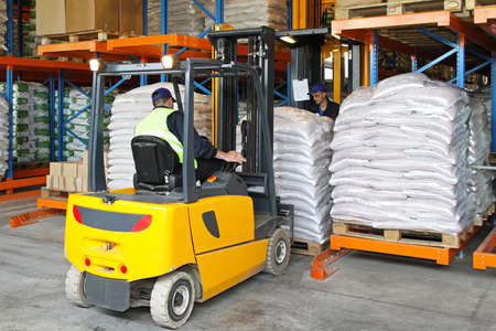 handling: Forklift driver handling goods in distribution warehouse