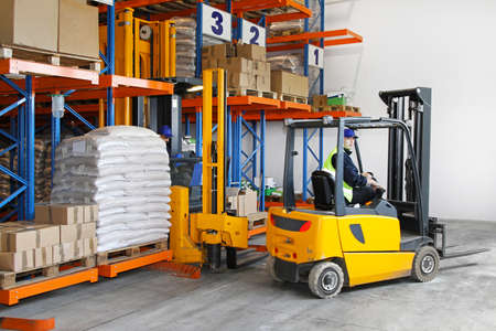 warehouse equipment: Two yellow forklift vehicles  in distribution warehouse Stock Photo