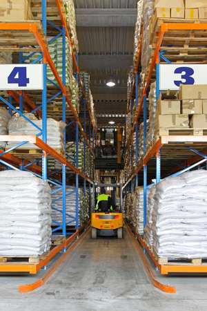 Yellow forklift in warehouse between shelves photo