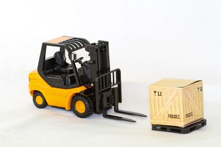 Miniature model of forklift with crate at pallet photo
