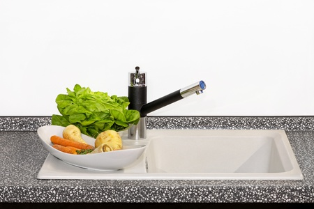Bowl of vegetables at modern kitchen sink photo