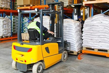 Forklift driver handling goods in distribution warehouse