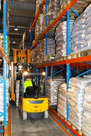 Yellow forklift in warehouse between racks photo