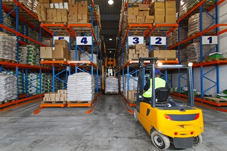 warehouse equipment: Forklift driver handling goods in distribution storehouse Stock Photo