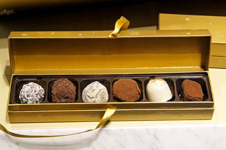 box of chocolates: Cholocate truffles in luxurious gold gift box Stock Photo