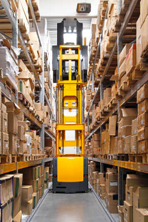 High rack stacker forklift truck in warehouse row photo