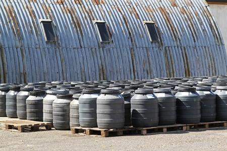 Chemical waste in plastic barrels near warehouse photo