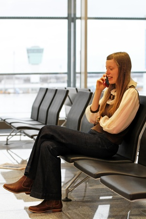 Girl at an airport making a call while waiting for her flight photo