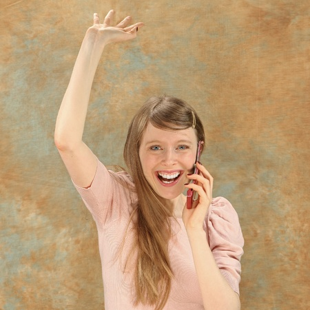 Excited young blonde girl with mobile phone photo