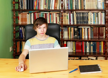 Teenage boy at desk with notebook computer in library photo