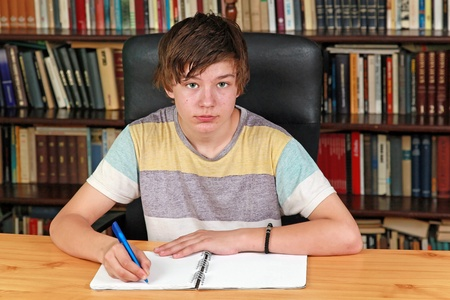 Teenage boy writing at desk in library Stock Photo - 13666339