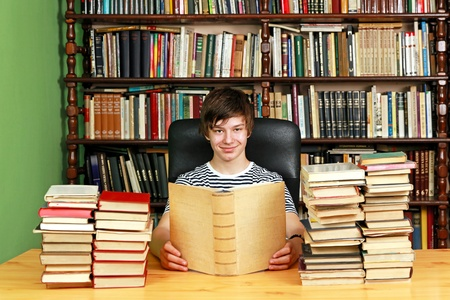 Young teenage boy reading in school library photo