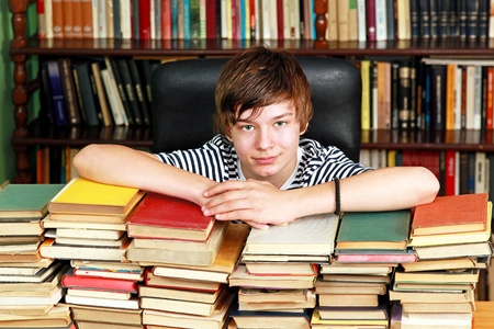 Young teenage boy with big pile of books in library photo