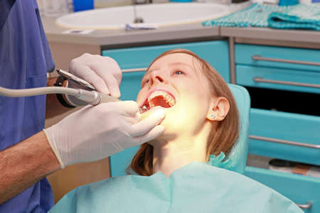 dentist drill: Young bloonde girl in dentist office chair Stock Photo