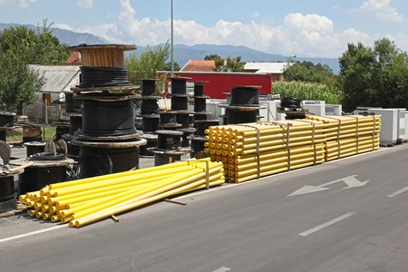construction material: Construction pipes and cable reels at open storage