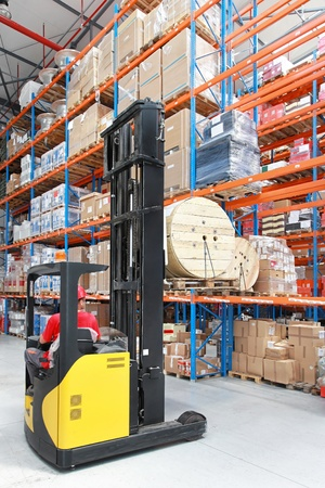 Forklift loading roll pallet in distribution warehouse photo