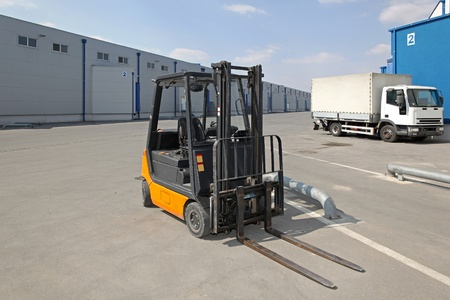 forklift truck: Forklift and truck in front of distribution warehouse
