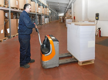 Worker loading pallet of paper with pallet jack photo