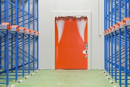 porte du congélateur de l'entrepôt couvert de givre et de glace