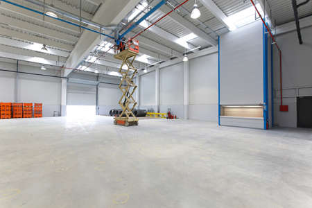 New distribution warehouse hall with hydraulic scissors lift platform Stock Photo