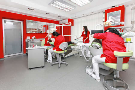 Zahnärzte bei der Arbeit in der modernen roten Zahnarztpraxis Lizenzfreie Bilder