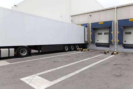 loading bay: White box semi trailer at warehouse loading bay Stock Photo