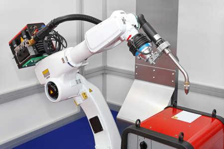 robot: Białe ramię robota do spawania w fabryce Zdjęcie Seryjne