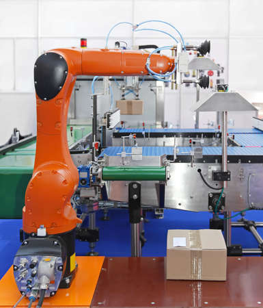 production line: Articulated robotic arm at packaging line in factory