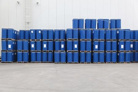 Pila di barili blu nella fabbrica chimica