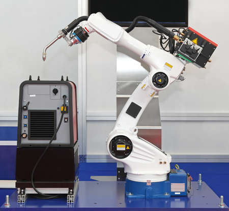 robot: White robotic arm for welding in factory