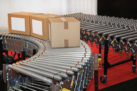 Powered conveyor rollers for transfer boxes in factory Stock Photo