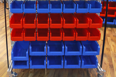 Red and blue plastic bins at sorting shelf in warehouse photo